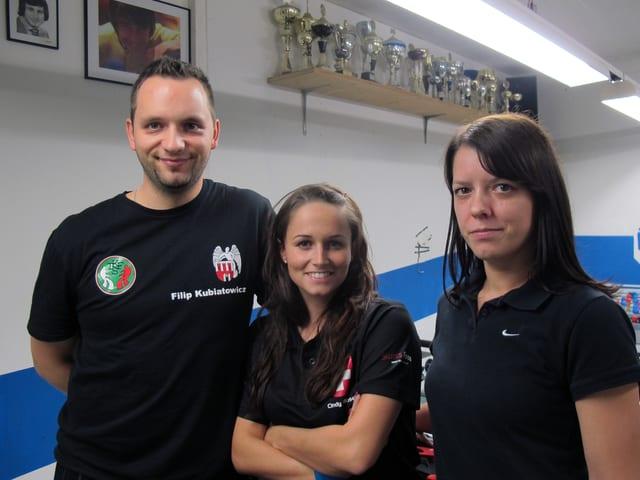 Ein Mann und zwei Frauen stehen vor Pokalen