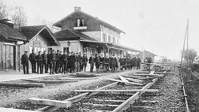 Mehrere Männer stehen an einem Bahnhof