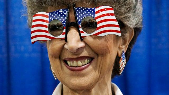 Eine ältere Frau mit einer US-Flaggen-Brille auf der Nase.