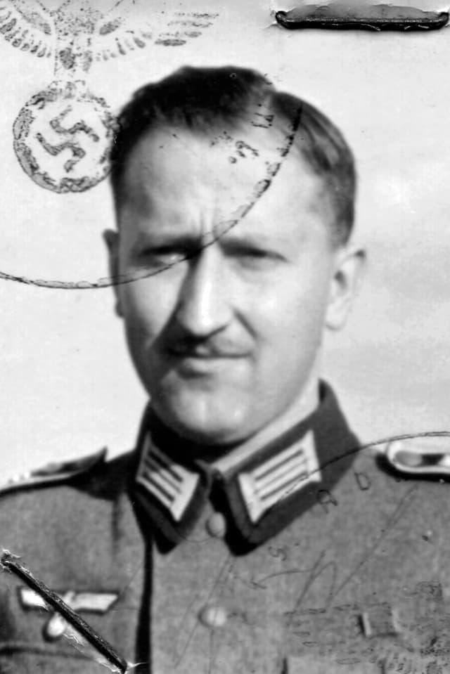 Ein Foto eine Mannes. Es trägt einen Stempfel mit einem Hakenkreuz.