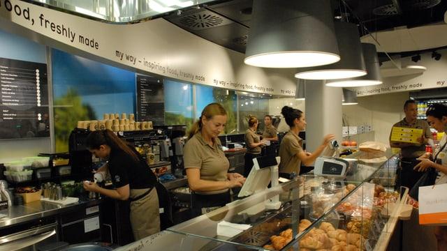 Theke mit Essen in der Auslage, Bedienung dahinter, Kunden davor, Kaffeemaschine. An der Wand der Schriftzug «inspiring food, freshly made».