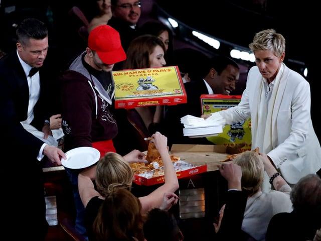 Die Moderatorin verteilt Pizzastücke