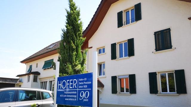 Gebäude mit Firmen-Schild im Vordergrund.