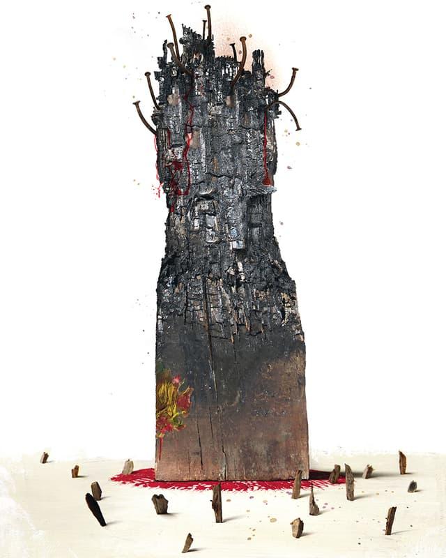 Ein angesengtes Holzscheit, aus dessen oberer Hälfte krumme Nägel ragen.