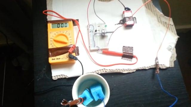 Eine Batterie, Drähte und ein Messgerät liegen auf einem Tisch.