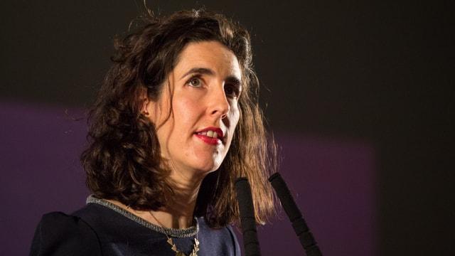 Eine Frau mit braunen langen Haaren vor dem Mikrofon.