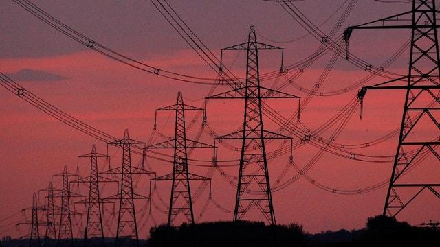 Strommasten reihen sich im Sonnenuntergang hintereinander auf.