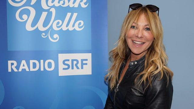 Rosanna Rocci steht vor dem SRF Musikwelle Logo.
