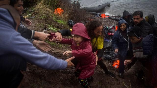 Zwei Männer helfen einem kleinen Mädchen eine Böschung hinauf, hinten weitere Bootsflüchtlinge am Ufer.