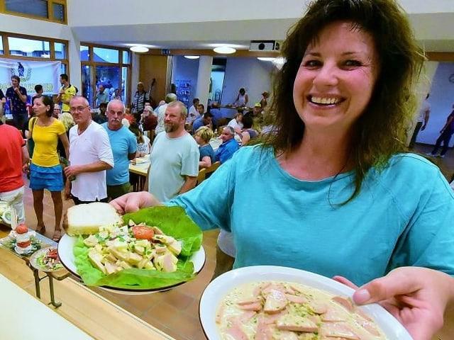 Frau hält Teller mit Wurstsalat.