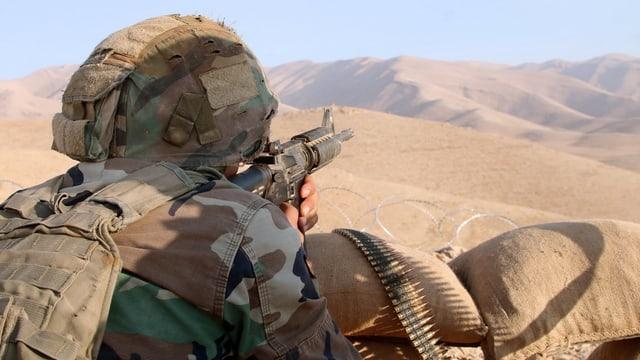 Soldat mit Gewehr, im Hintergrund Wüste.
