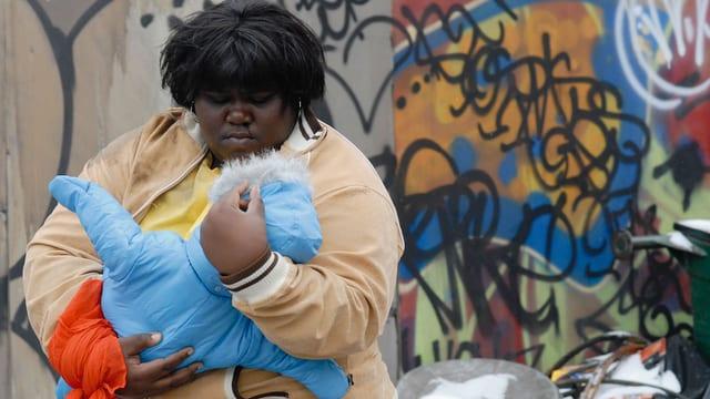 Schwarze, dicke Frau trägt Baby auf dem Arm, im Hintergrund eine Graffity-Wand