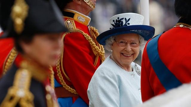 Die Queen lächelnd in einem weissen Kostüm mit Hut.