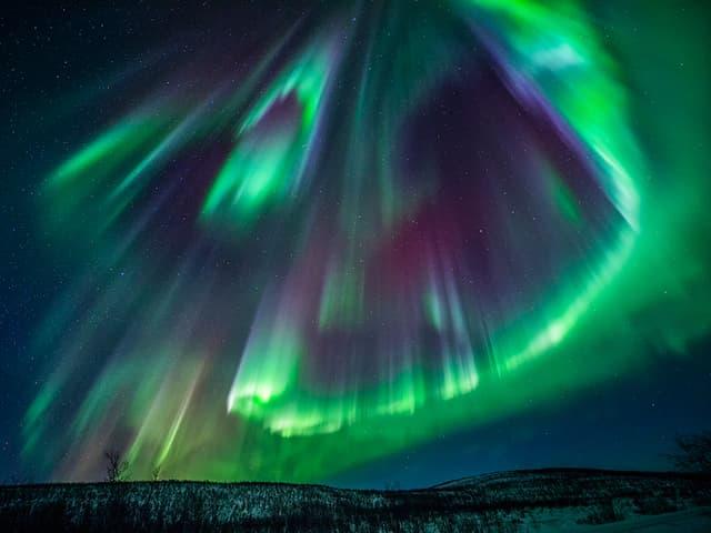 Nachthimmel mit kitschigem Polarlicht in grün, violett und gelb. Säulenförmig von oben nach unten.