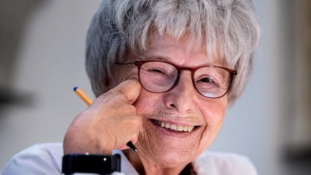 Eine Frau mit grauem Haar, Brille und einem Stift in der Hand.