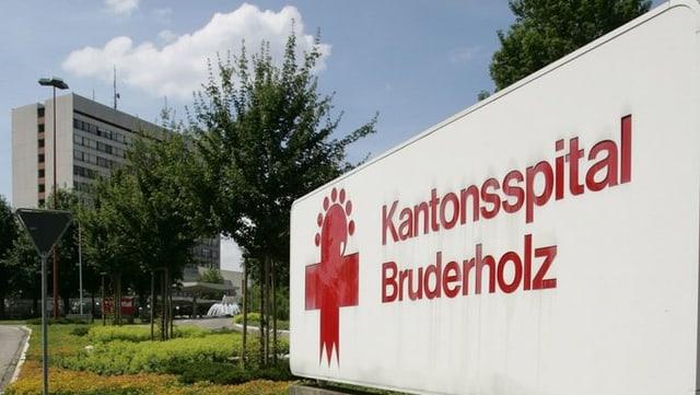 Schild Bruderholz Spital, im Hintergrund der Spitalbau.