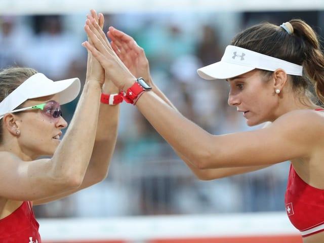 Nadine Zumkehr und Joana Heidrich berühren sich am Netz mit den Handflächen.