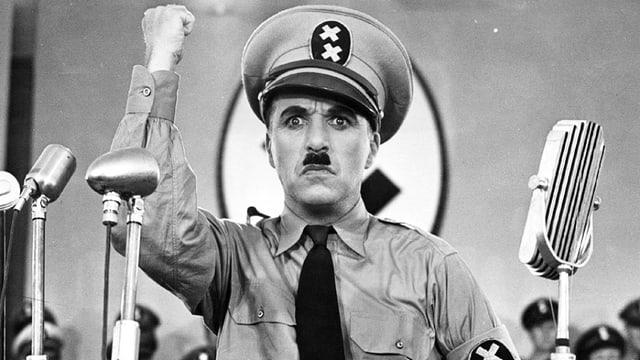 Charlie Chaplin, verkleidet als Adolf Hitler, steht vor Mikrofonen und streckt mit strenger Mine die Faust in die Luft.
