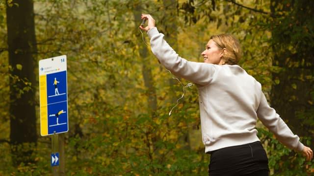 Zu sehen ist SRF 3 Moderatorin Kathrin Hönegger beim Joggen im Wald. Sie hält ein Smartphone in der Hand, ein Kopfhörer-Stöpsel ist im rechten Ohr, der zweite Ohrstöpsel ist rausgefallen. Links im Bild ist eine Vita-Parcours Tafel zu sehen.
