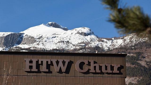 Die Beschriftung am Gebäude der HTW, im Hintergrund der Gipfel des verschneiten Felsberger Calanda.