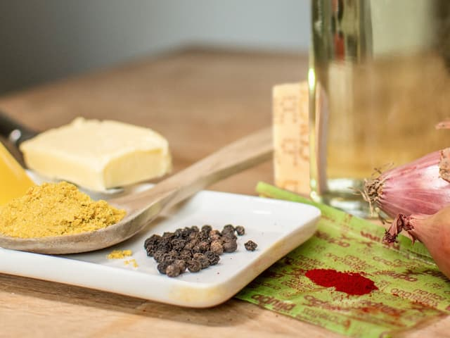 Auf einem Tisch liegen Pfefferkörner, Butter, Zwiebeln, Weisswein, Risotto-Reis, Käse und Safran.