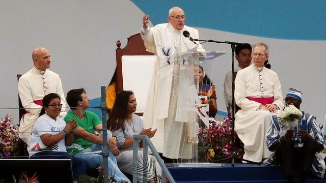 Papst Franziskus auf einem Podium vor einem Rednerpult.