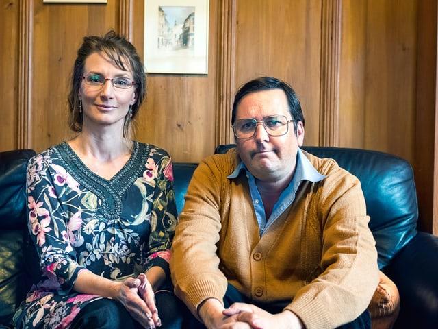 Ein Mann und eine Frau sitzen auf einem schwarzen Sofa.