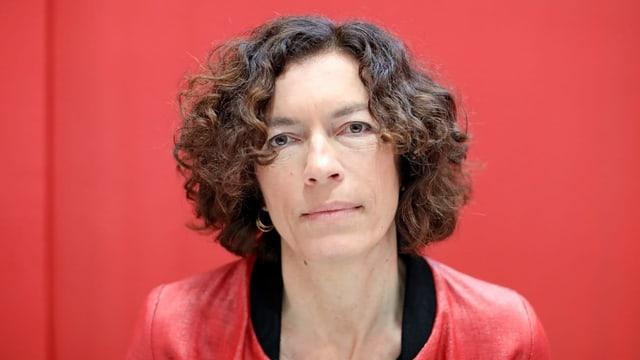 Porträtaufnahme einer Frau mit dunklen Haaren vor einem roten Hintergrund