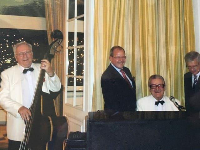Vier ältere Herren hinter einem Klavier.