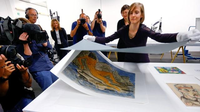 Eine Frau hebt ein Deckblatt von einer Zeichnung ab. Pressefotografen fotografieren.