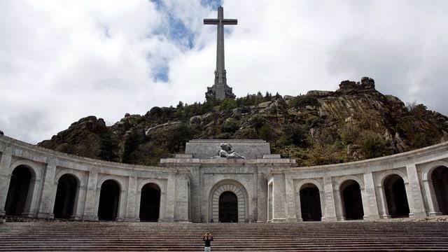 Eine Person auf dem grossen Platz vor dem Mausoleum mit Kreuz.