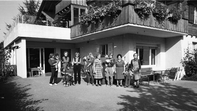 Schwarzweiss-Bild eines Hauses (Kinderheim), davor stehen einige Kinder und Frauen.