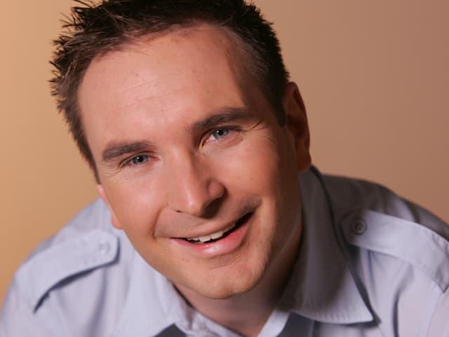 Der Moderator trägt ein helles Hemd und posiert vor einem braunen Hintergrund.