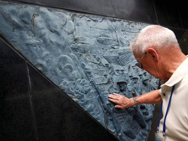 Person berührt ein Relief an einem Gedenkstein.