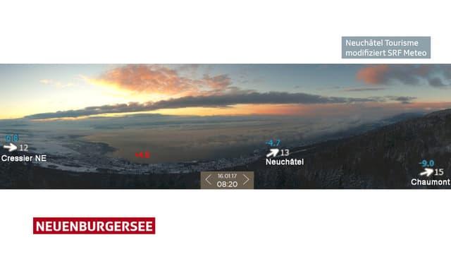 Blick vom Chaumont hinunter in das Mittelland. Am linken Ende des Neuenburgersees hat es keine Wolken, am rechten Ende viele Wolken.