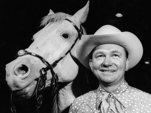 Tex Ritter mit Cowboy-Hut neben einem Pferd