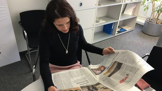 Eine Frau in schwarzem Oberteil sitzt an einem Tisch und blickt in eine Ausgabe des Tages-Anzeigers.