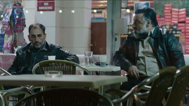 Stratos sitzt zusammen mit dem Gangsterboss ausserhalb eines Restaurants.