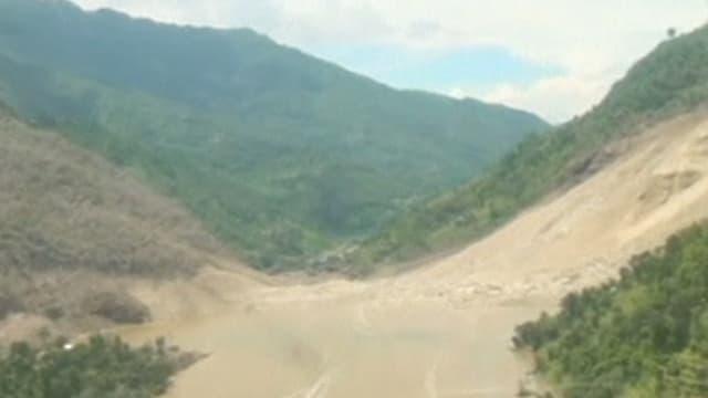 Blick aus einem Helikopter auf die Abbruchstelle und den gestauten Fluss.