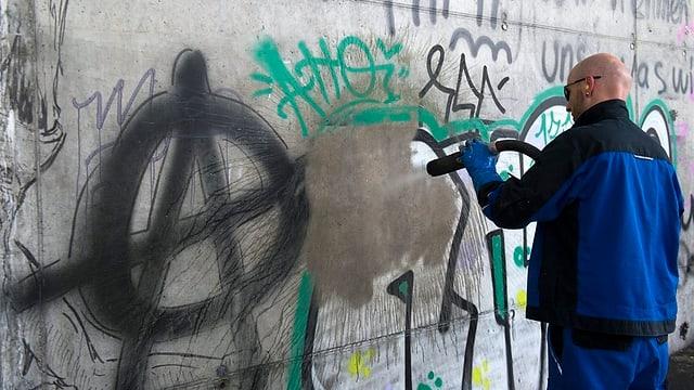 Mann beseitigt Sprayereien an einer Mauer mit einem Hochdruckreiniger.