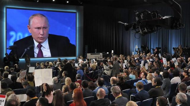 Grosser Raum mit Journalisten. Auf einem Bildschirm ist Putin zu sehen.