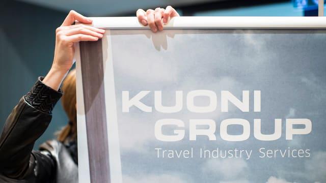 Ina persuna che tegn in placat dal concern da viadis Kuoni.