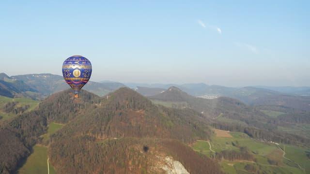 Hügelige Landschaft bei wolkenlosem Wetter. Recht klein ist ein Heissluftballon sichtbar.