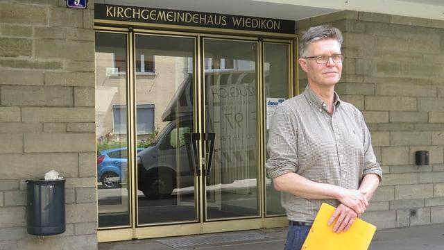 Mann mit gelber Mappe vor Glastüre