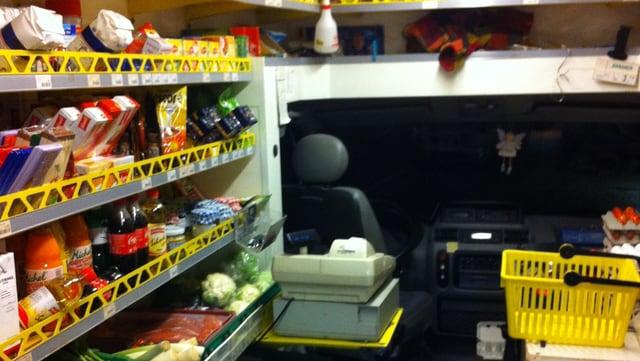 Ein Bus von Innen, an den Seitenwänden Regale mit Lebensmitteln.