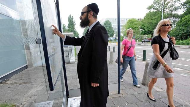 Ein Jude in traditionellem Ornat steht an einer Bushaltestelle, Passanten gehen vorbei