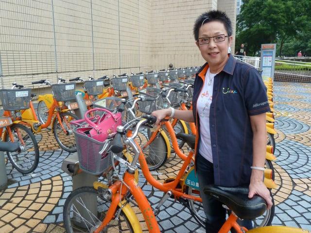 Eine mittelalterliche Taiwanesin mit Kurzhaarschnitt und Brille steht neben einem Fahrrad.