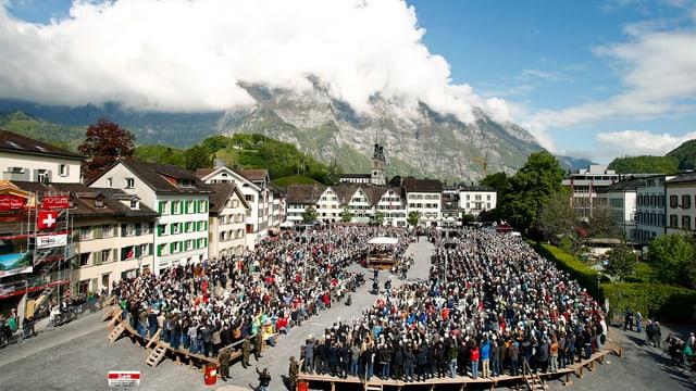Glarner Landgemeinde mit versammelter Menschenmenge und Häusern und Bergen in Wolken im Hintergrund.