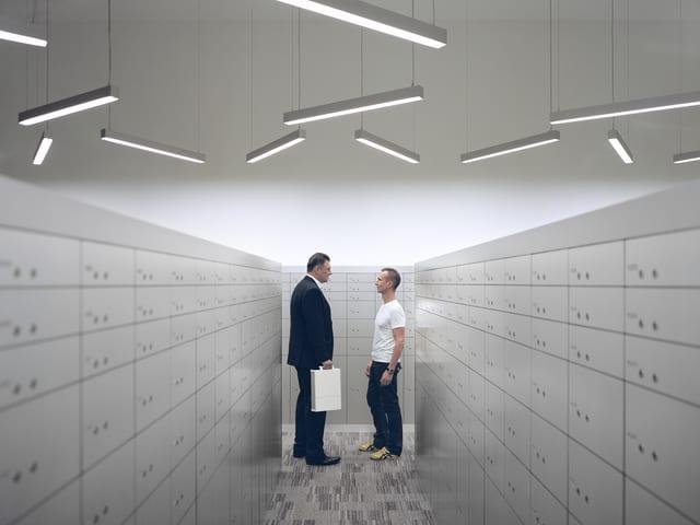 Zwei Männer stehen zwischen Fächern und schauen sich an.