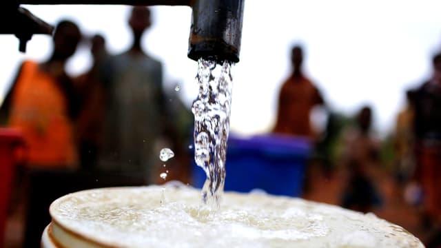 Aus einem Wasserhahn fliesst klares Wasser in einem alten Eimer. Im Hintergrund stehen afrikanische Menschen.